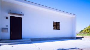 白い壁のキューブビックなお家。アクセントの玄関ドアと四角い窓が可愛い。遊び心のある家、行橋平屋のbe-plus。