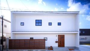 キュービックな二階建ての白いスタイリッシュな家。アクセントの真四角なまどと、かわいい玄関扉。エコサームを利用したパッシブデザインの家。