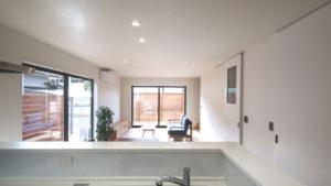 白で統一された、壁、建具、天井、キッチンとリビングから広がる屋外居住空間のウッドデッキ。パッシブデザイン2階建ての家。
