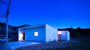 格子窓からもれる黄色い明かり。シンプルなC形の家。遊び心あふれるbe-plusu、パッシブデザインの家。
