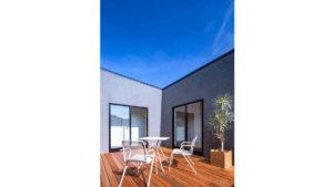 青い空にグレーのCスタイルの家。シンプルスタイリッシュなこの家は、be-plusのパッシブデザインの家。家の中央のウッドデッキの、白い机と白い椅子。お天気のいい日は、中庭でブレックファースト。
