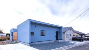 青いシンプルなコの字形の家は、パッシブデザイン、be-plusの平屋住宅。コの字形の屋内空間と挟まれたウッドデッキの屋外空間のある家。夏涼しく、冬あたたかなエコハウス。