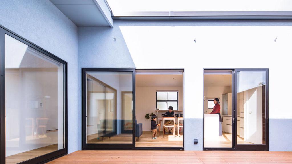 コの字形の内側は、黒いサッシの大きな窓があり、リビングやお部屋からそのまま屋外空間へ行くことが出来る。リビングとつながるフラットなウッドデッキで、リビングがとても広く感じられる。パッシブデザイン、be-plusの家。