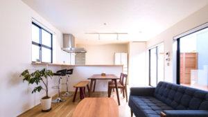 キッチン、ダイニングテーブル、ソファーとつながるライン。ホワイトの壁と天井、ナラ樫のフロアーがナチュラル。グレイッシュブルーのソファーがアクセント。ウッドデッキから明かりが入る明るい家。パッシブデザインの平屋住宅。