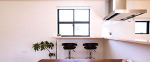 キッチンのカウンターからL字につくられた、遊び心のあるスペースは、足の長い可愛い椅子と格子窓で、カフェ気分が味わえる。ヤスナグデザインホーム株式会社の家。