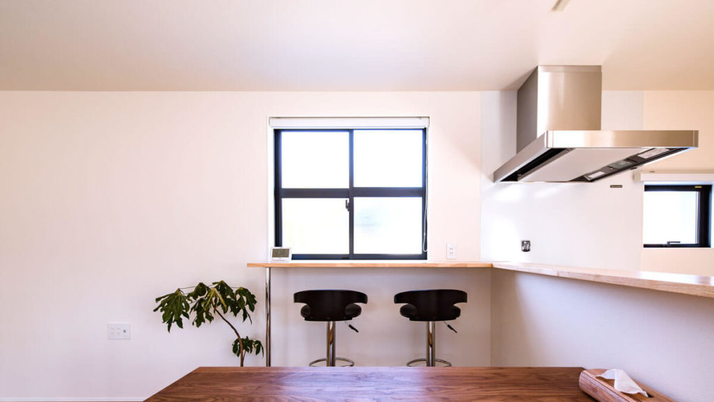 キッチンからつながるカウンターは、L字形。黒いサッシの格子の窓からはいる明るく落ち着いた光。カウンターに添えられた、足の長い黒い椅子が2脚。楽しいおしゃべりの余韻。パッシブデザインbe-plus。