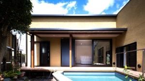 L字形の家の中庭は、鯉が泳げる池つき。自然を感じながら楽しめる老後。からし色の塗り壁が和風な趣を醸し出している。落ち着きのあるヤスナグデザインホーム株式会社の家。