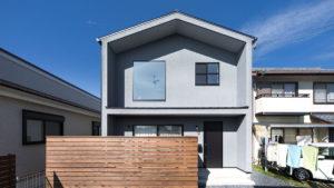 三角屋根の塗り壁の家は、パッシブデザイン、be-plusの家。夏涼しく、冬暖かな家。グレーの外観と大きな窓、玄関横に外空間を楽しめるウッドデッキがある。