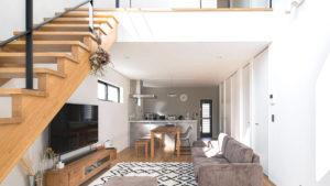 幾何学模様のラグで、落ち着きのあるグレーのソファー。キッチン側の壁はワンポイントになるよう色をライトグレーの壁紙に変えた。シンプルスタイリッシュに決める、be-plusの2階建て住宅