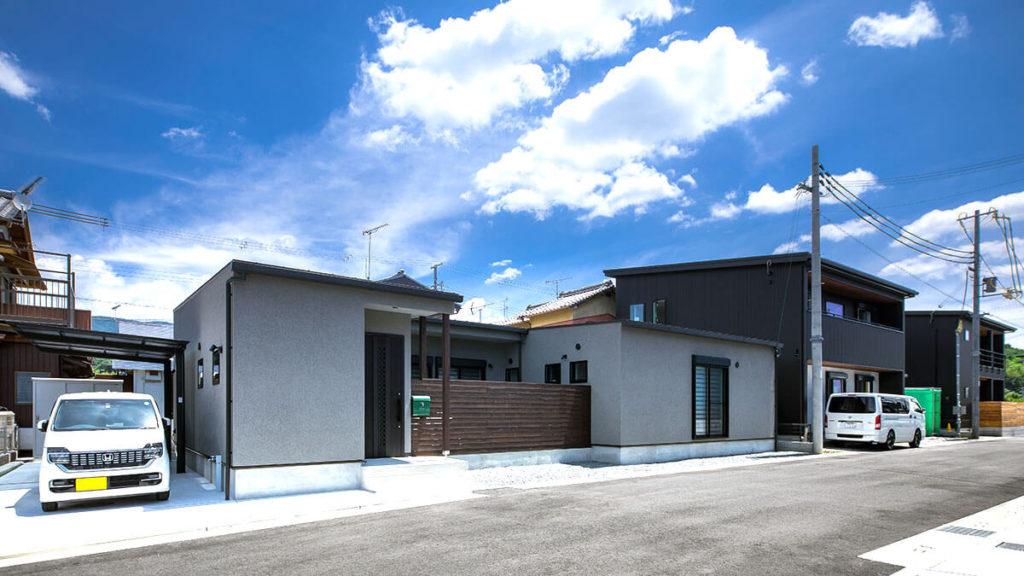 グレーのコの字形の家は、be-plusのパッシブデザインの家。コの字形の家は、中央から自然のエネルギーを部屋の中に通す。