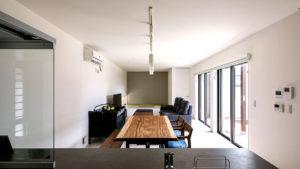 シンプルな白い壁に一枚板のリビングテーブル。ダークグレーのソファーを置く。中庭からの明かりで優しく包まれたリビング。