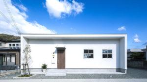 四角くシンプルなお家。白い塗り壁が印象的。玄関ドアの木目がアクセント。白い格子窓が2つ並んでいる。
