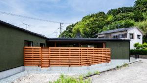L字型のモスグリーンの塗り壁にウッドデッキで囲まれた中庭のある家。be-plusパッシブデザインの平屋住宅。