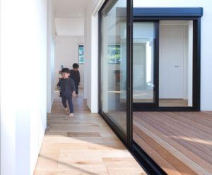 行橋、苅田の平屋住宅、ヤスナグデザインホームが販売するbe-plusのOスタイルは、中央に中庭があるパッシブデザインの家。回遊できる廊下を子供達がぐるぐる回って遊んでいる。