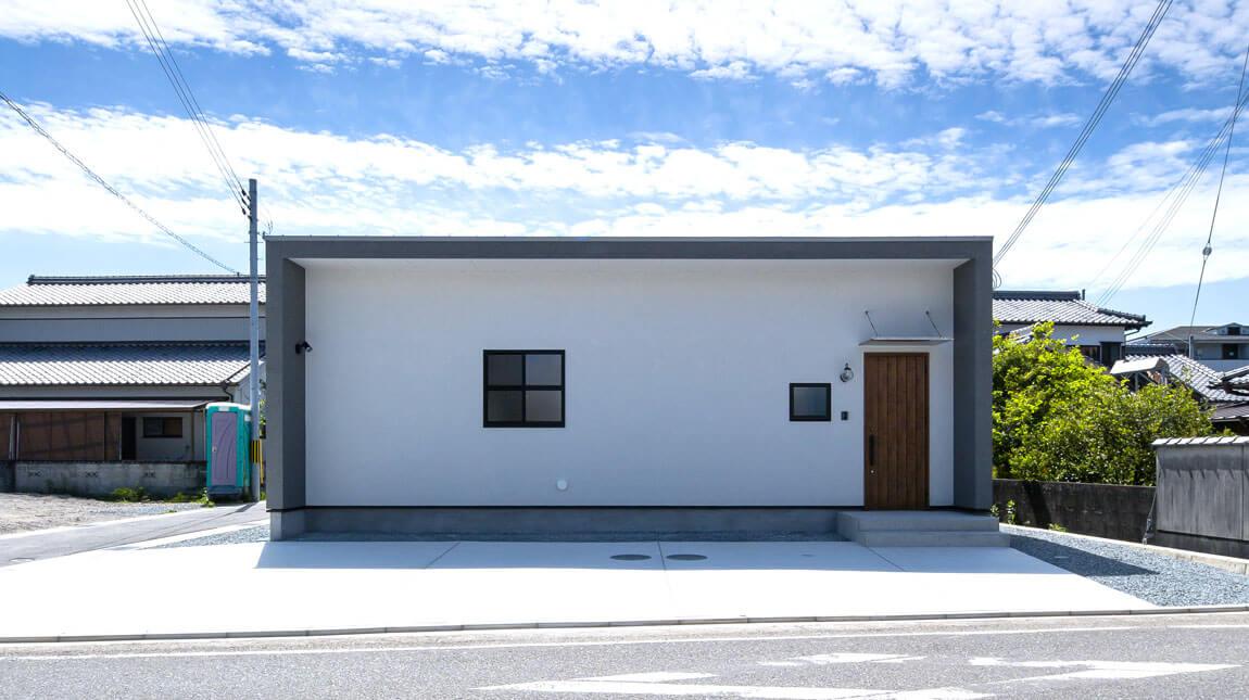 四角いシンプルな玄関。外回りに窓をあまりもうけず、プライバシーを守れる中庭から光と風を取り入れている、パッシブデザインの平屋住宅。