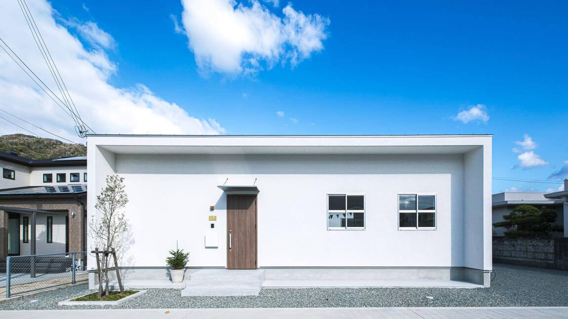 四角くスタイリッシュな塗り壁の白い家。