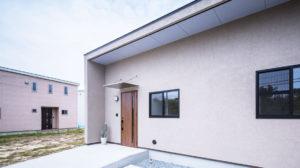 ライトグレーの塗り壁のシンプルな四角い家は、行橋、小倉、苅田におすすめの平屋住宅、ヤスナグ