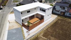 白いパッシブデザインのLの字形の家。