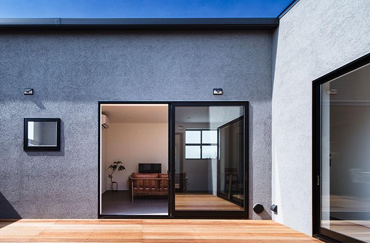 グレーの特殊なW断熱の塗り壁の家。中庭のウッドデッキからリビングを除いた景色。窓には、カーテンが無い。カーテンの要らない家はヤスナグデザインホーム。北九州・行橋・苅田の平屋。