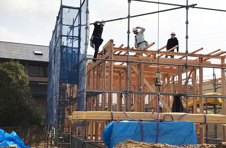 たくさんの大工さんで棟上げ。コの字形の家は、ヤスナグデザインホーム。
