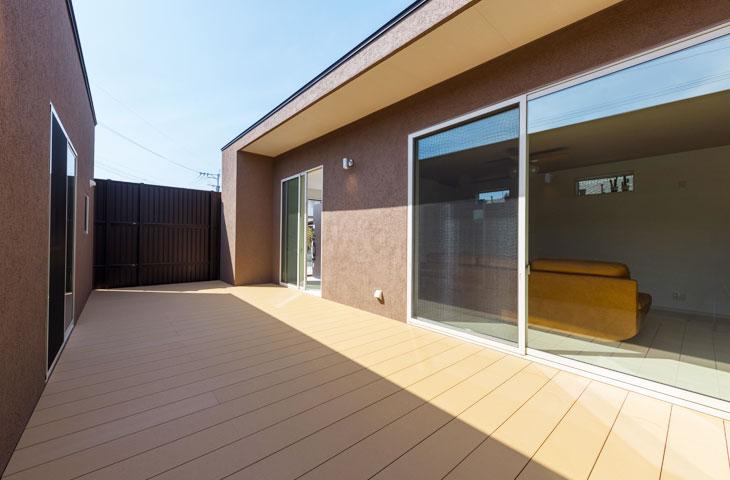 ウッドデッキの中庭にお日様があたっている。ブラウンの塗り壁に大きな窓が開放的。塀があるので、プライバシーも守れて安心。