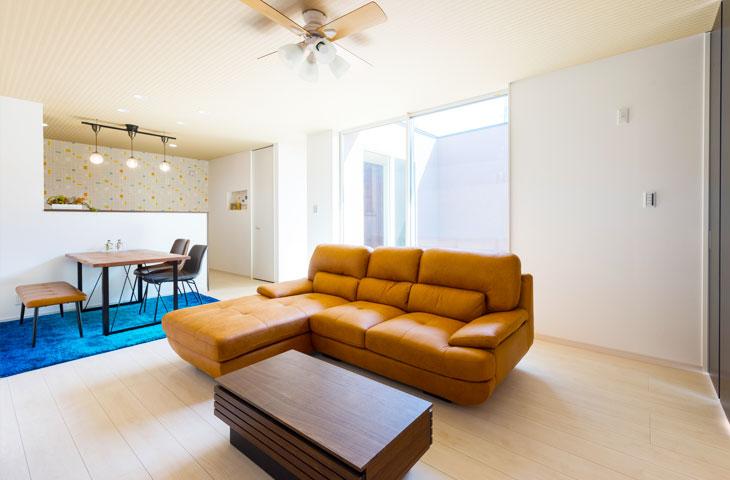 明るいブラウンの大きなソファーとカウンターのあるキッチン。