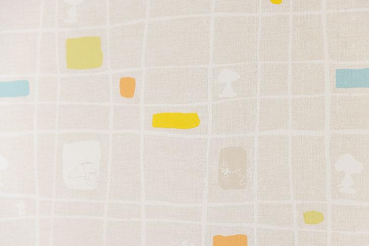 サンゲツのスヌーピー壁紙、RE51570は織物調の生地に黄色やオレンジ、グレー、ベージュ、水色などの様々な形のスクエアーが描かれている。