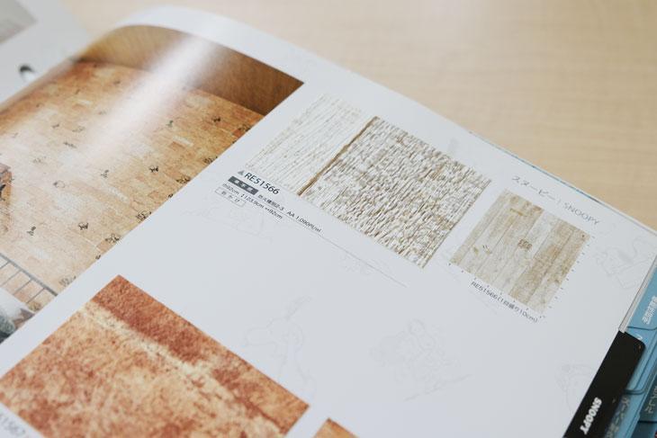 サンゲツの壁紙ブルー表紙のReSERVEカタログのスヌーピーページ白い木目調の壁紙。スヌーピーが違和感なく描かれている。