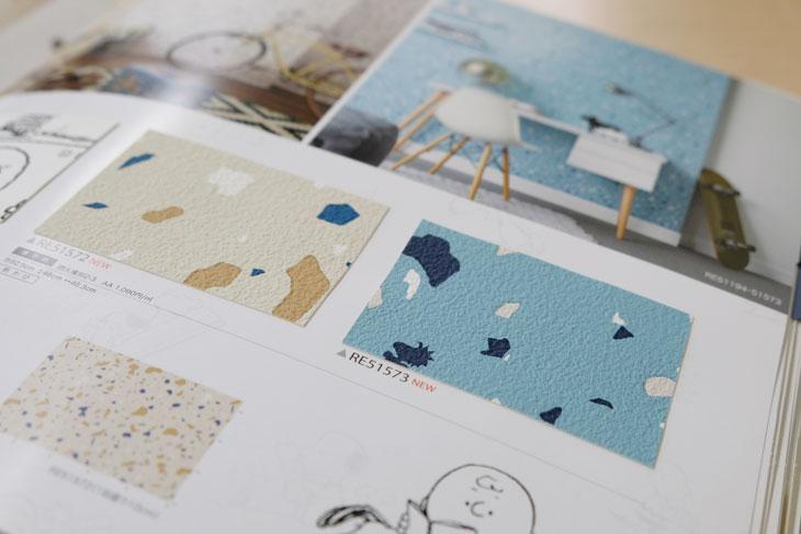 サンゲツの壁紙ブルー表紙のReSERVEカタログのスヌーピーのページ。水色とアイボリーの壁紙。スヌーピー柄だけど、おしゃれ感がある壁紙。