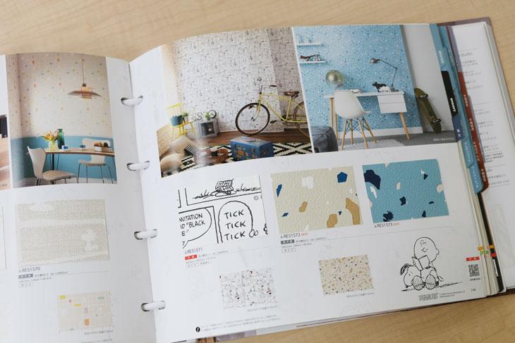 サンゲツの壁紙ブルー表紙のReSERVEカタログ、スヌーピー柄のページ、POPなデザインが子供部屋にぴったり。