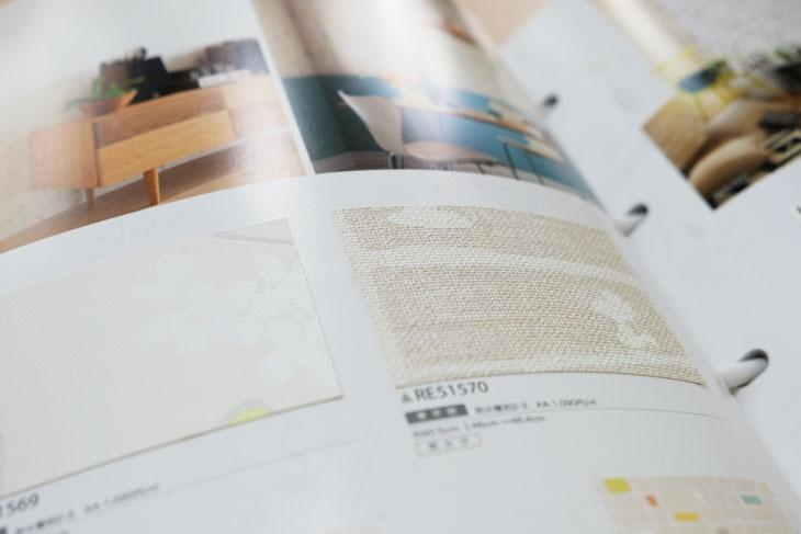 サンゲツの壁紙ブルー表紙のReSERVEカタログ、スヌーピー柄のページ。アイボリーとホワイトでナチュラル。使いやすいスヌーピー壁紙。